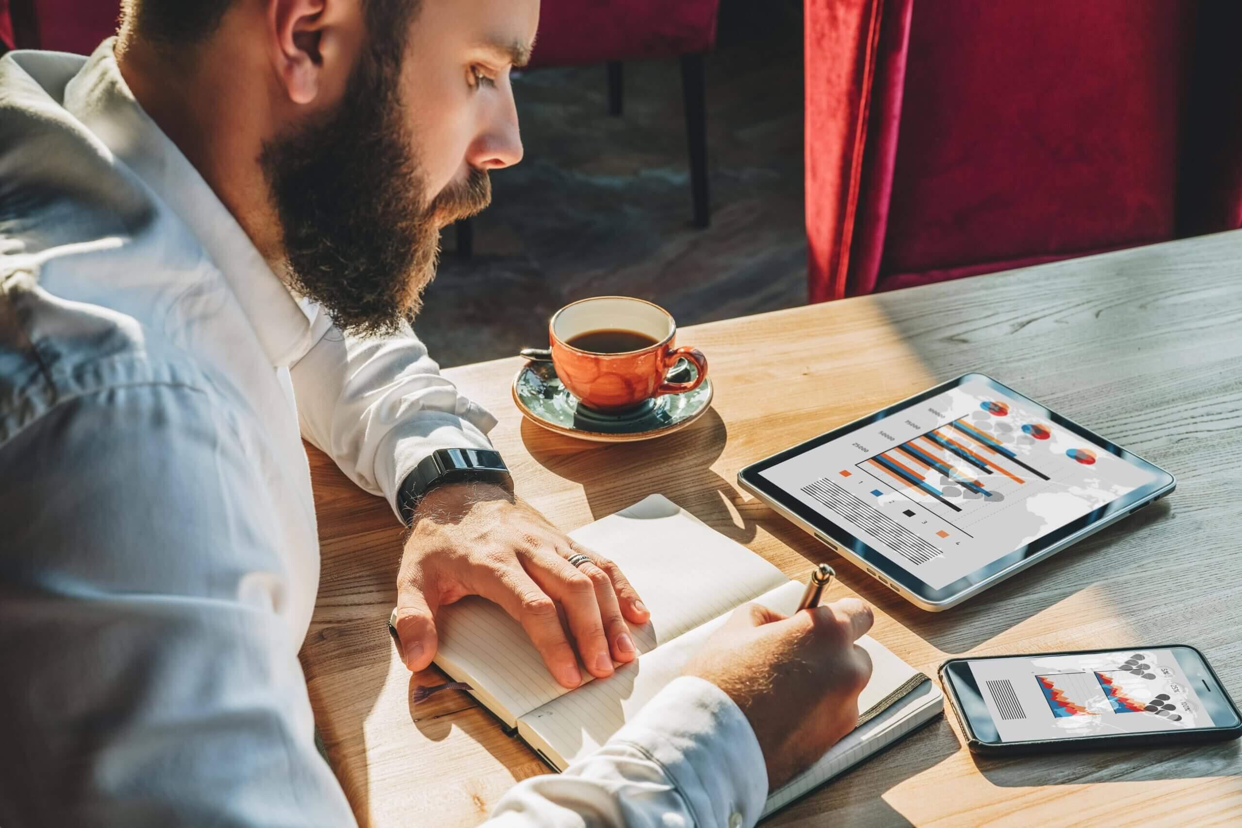Homem escrevendo carta personalizada em caderno.