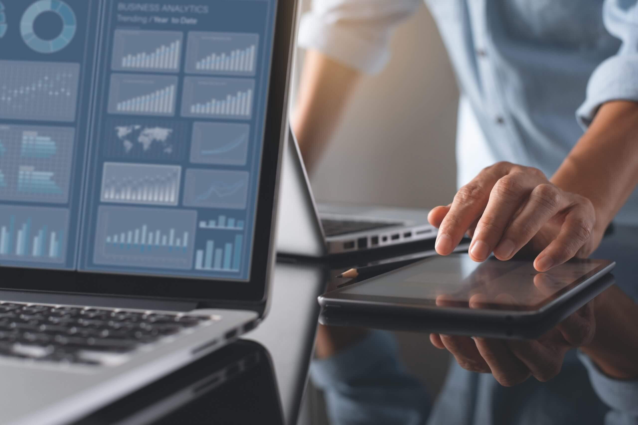 Pessoa analisando dados do usuário no computador e no tablet.