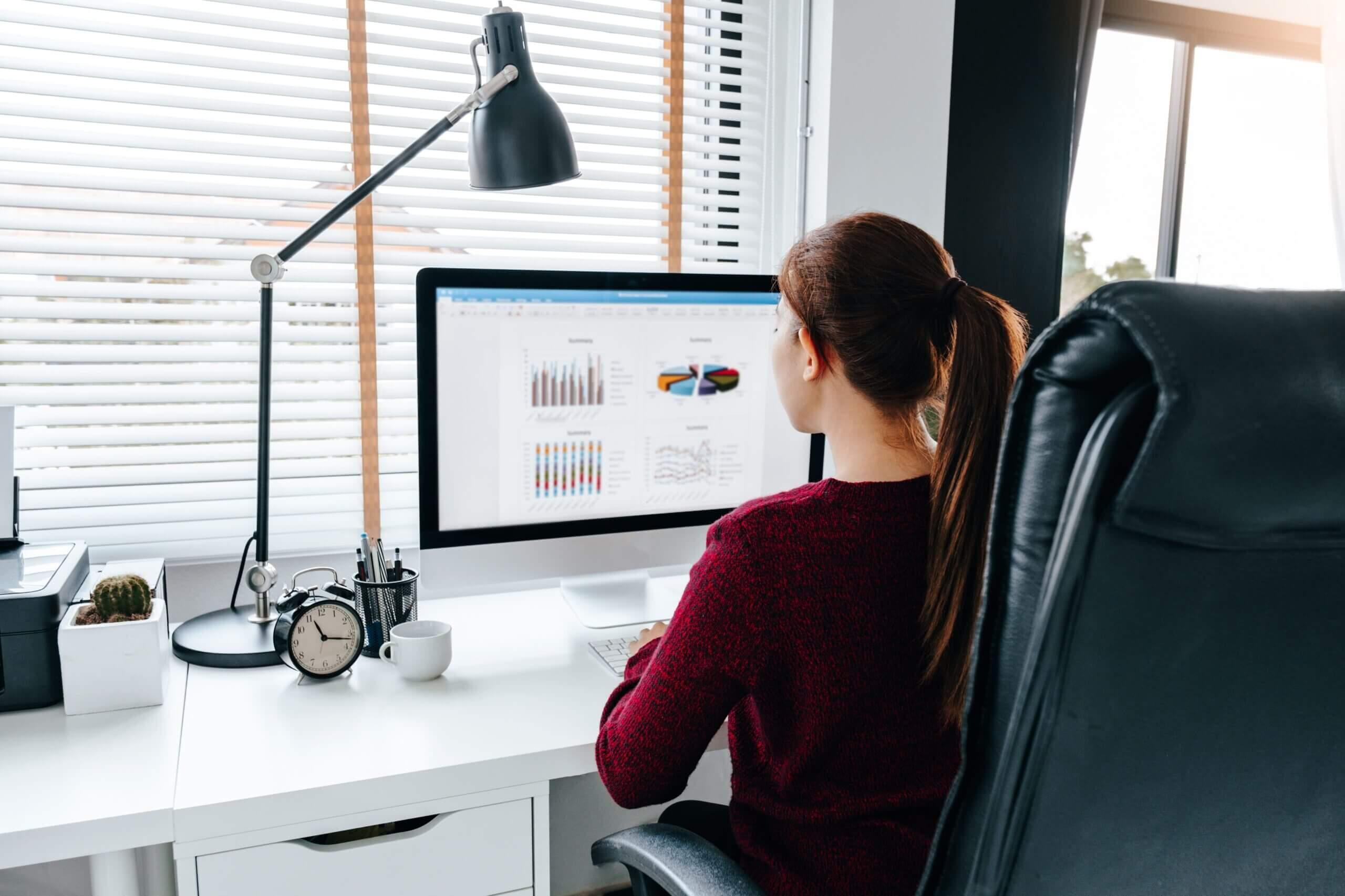 Mulher sentada em seu escritório, mexendo ao computador, de costas para a fotografia.