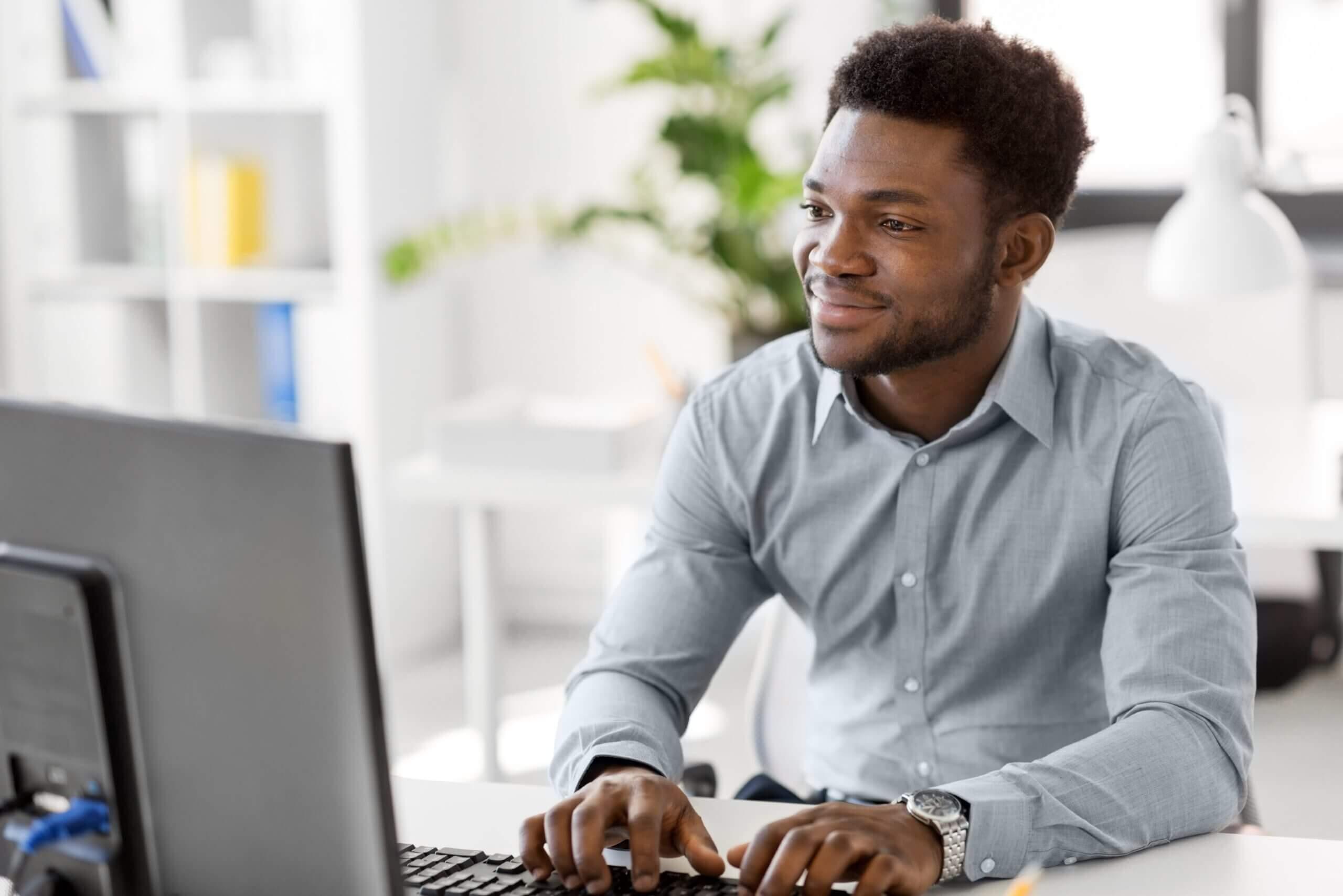 Home negro ao computador, sorrindo.
