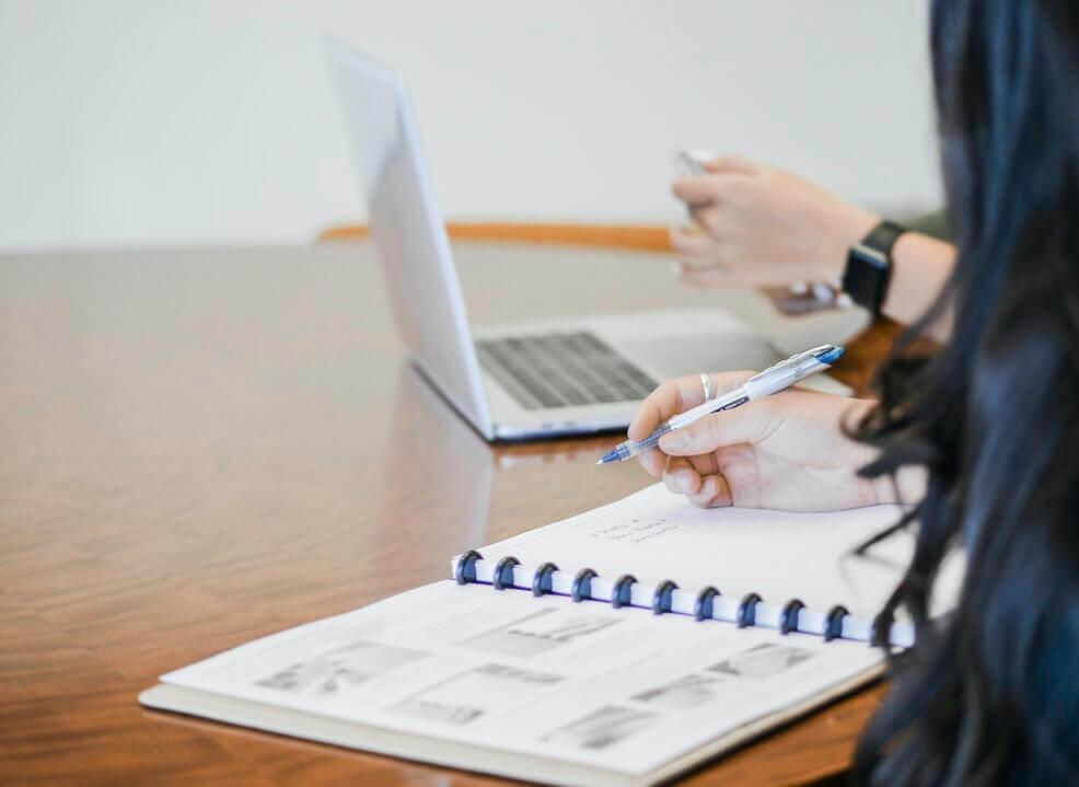 Mulher fazendo anotações em calendário enquanto outra mexe no computador.