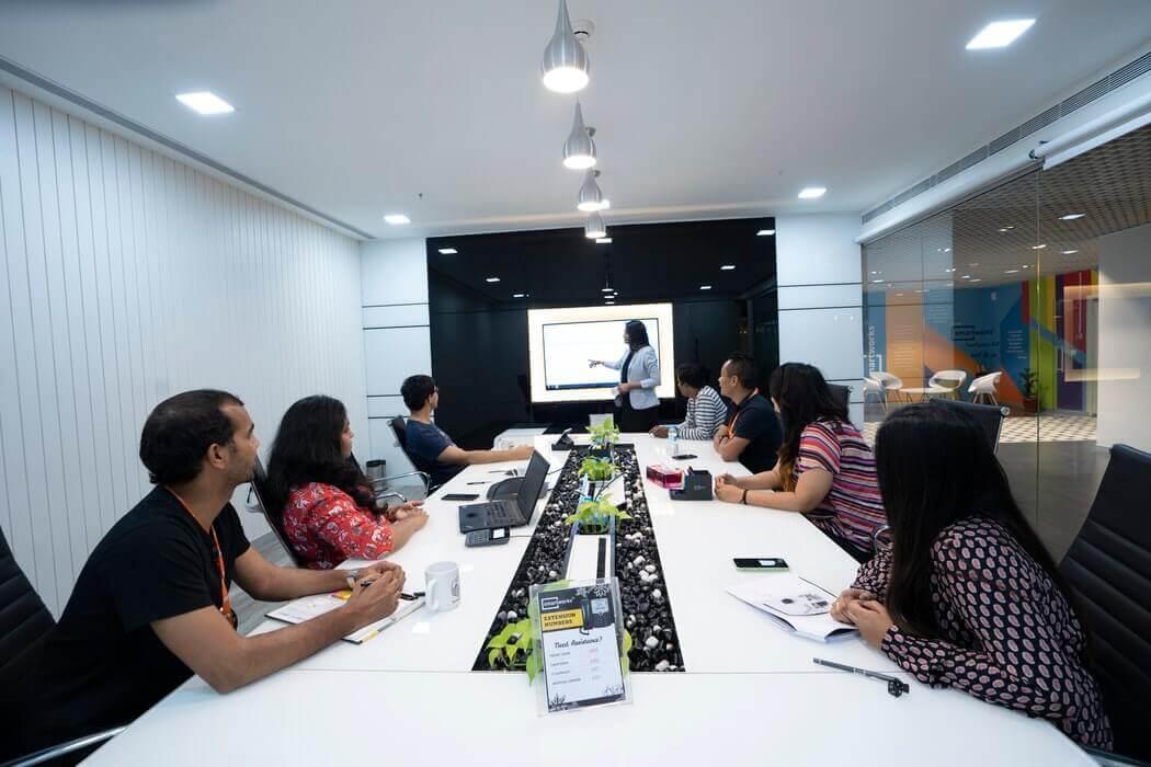Equipe de trabalho reunida em uma mesa, em treinamento.
